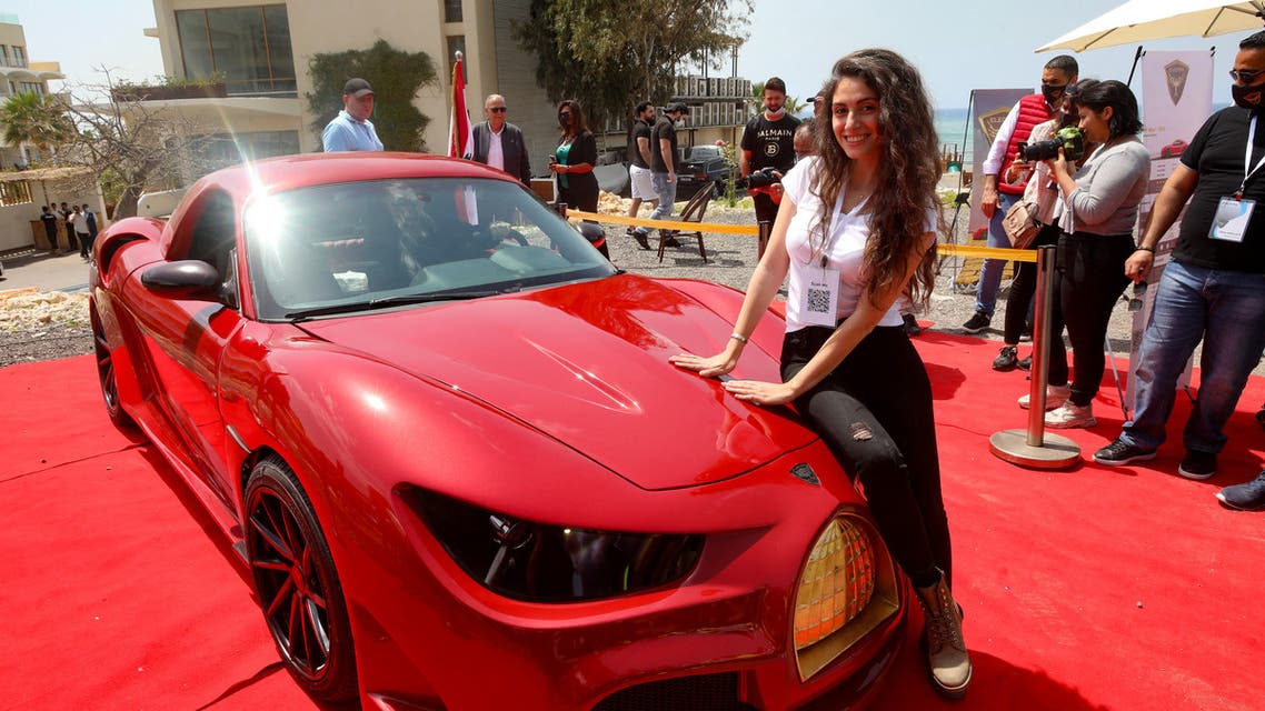 A model leans on the hood of the Quds Rise, the first ever electric car produced in Lebanon, during an unveiling ceremony in Khaldeh, south of the capital Beirut, on April 24, 2021. The front golden grille represents Al-Aqsa mosque's Dome of the Rock in Jerusalem. The lebanese-made electric car made its debut in a double first for the Mediterranean country that has never manufactured automobiles and is wracked by economic crisis and power cuts. (AFP)
