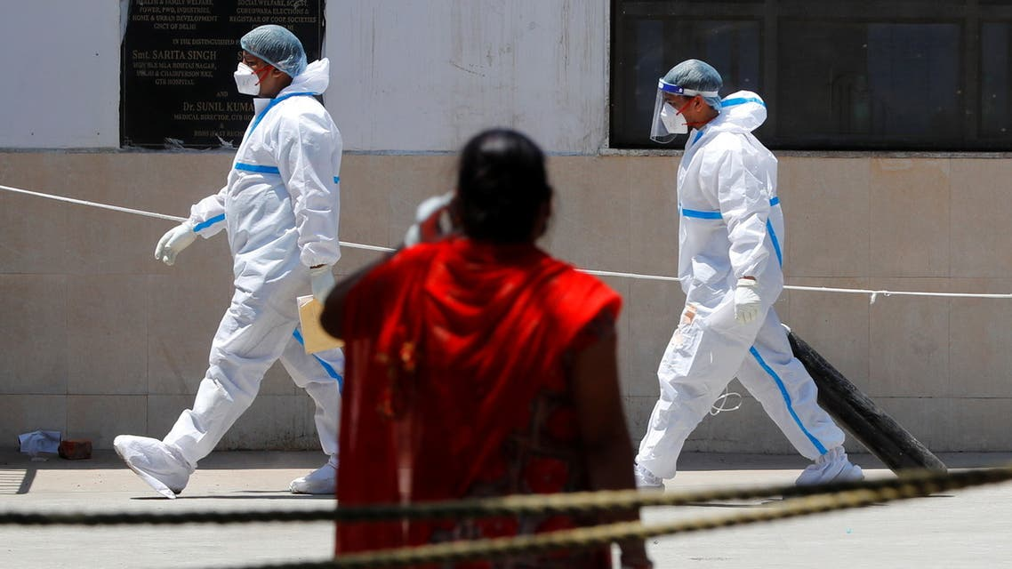 A health worker wearing personal protective equipment (PPE) carries an oxygen cylinder into the casualty ward at Guru Teg Bahadur Hospital, in New Delhi, India, April 24, 2021. (Reuters)