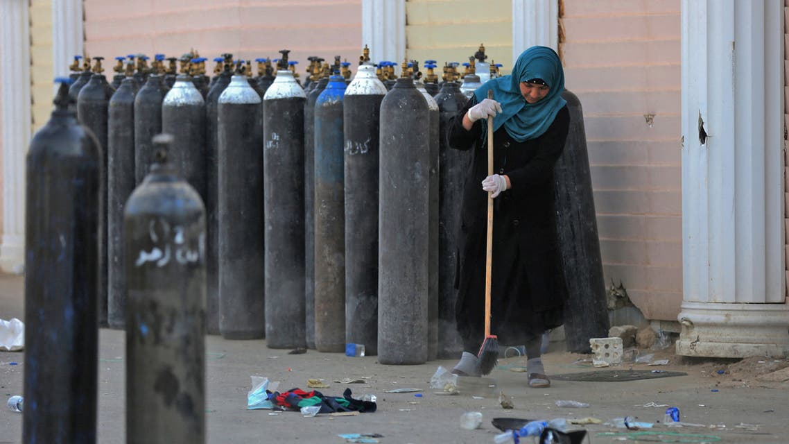 An Iraqi woman cleans debris next to evcuated oxygen bottles outdoors at the Ibn Al-Khatib Hospital in Baghdad, on April 25, 2021, after a fire erupted in the medical facility reserved for the most severe coronavirus cases. (AFP)