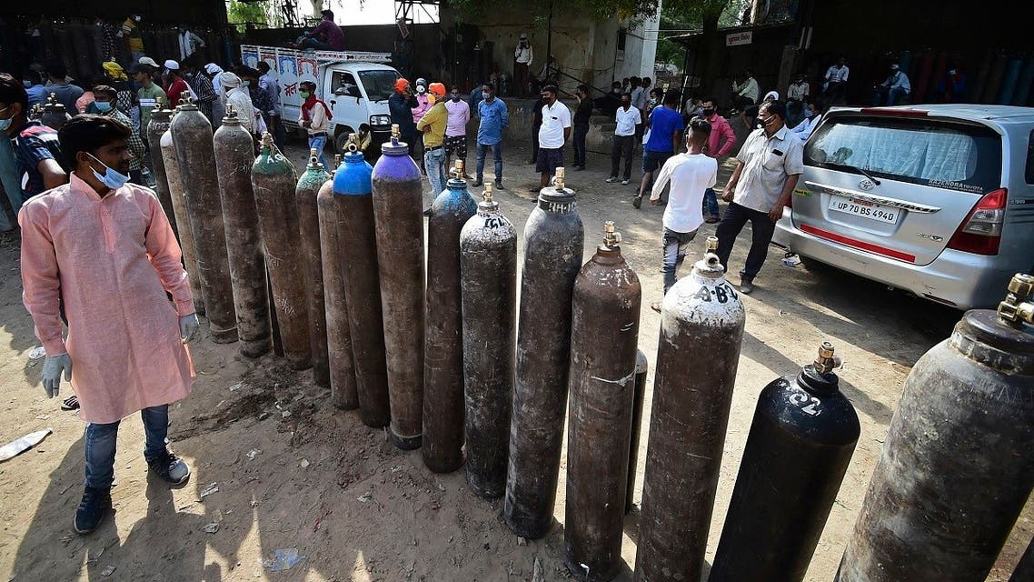 People wait to refill their medical oxygen cylinders for COVID-19 coronavirus patients at an oxygen refilling station in Allahabad on April 24, 2021. (Sanjay Kanojia/AFP)