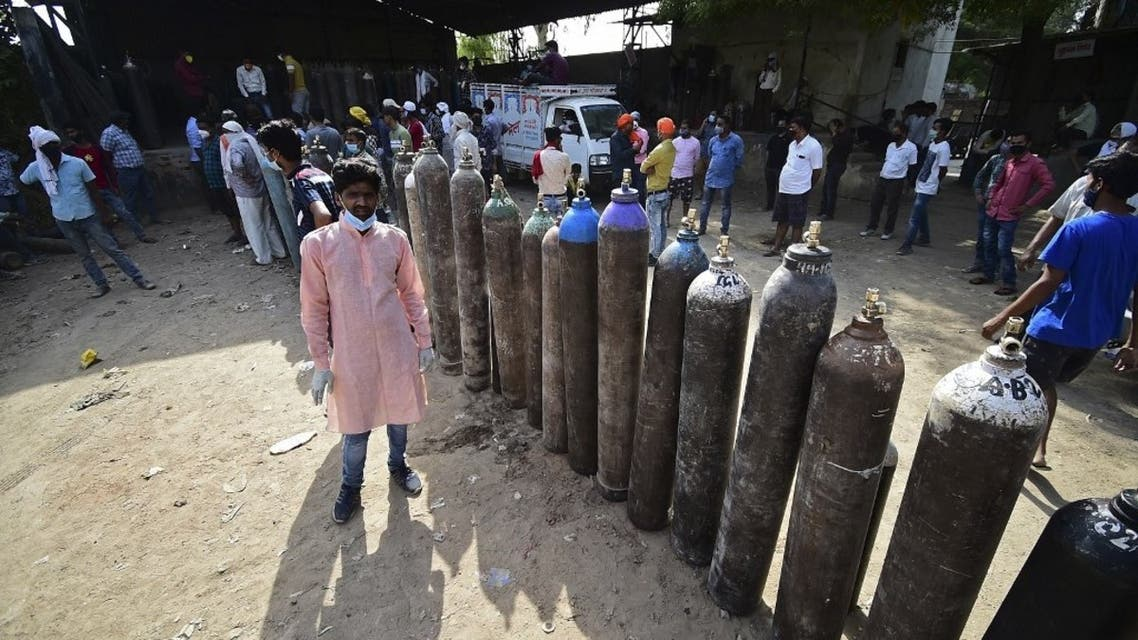 People wait to refill their medical oxygen cylinders for Covid-19 coronavirus patients at an oxygen refilling station in Allahabad on April 24, 2021. (AFP)