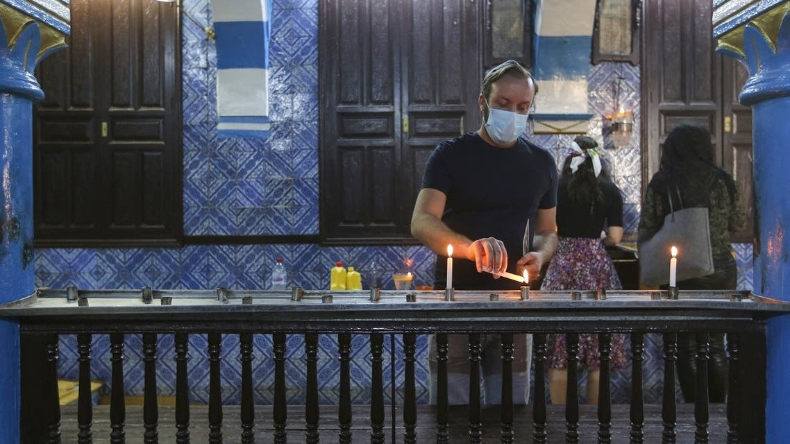 A Tunisian Jewish pilgrim lights a candle on the first day of the annual pilgrimage to the Ghriba Synagogue, the oldest Jewish monument built in Africa, on April 26, 2021 in the Mediterranean Tunisian resort island of Djerba. (Fathi Nasri/AFP)
