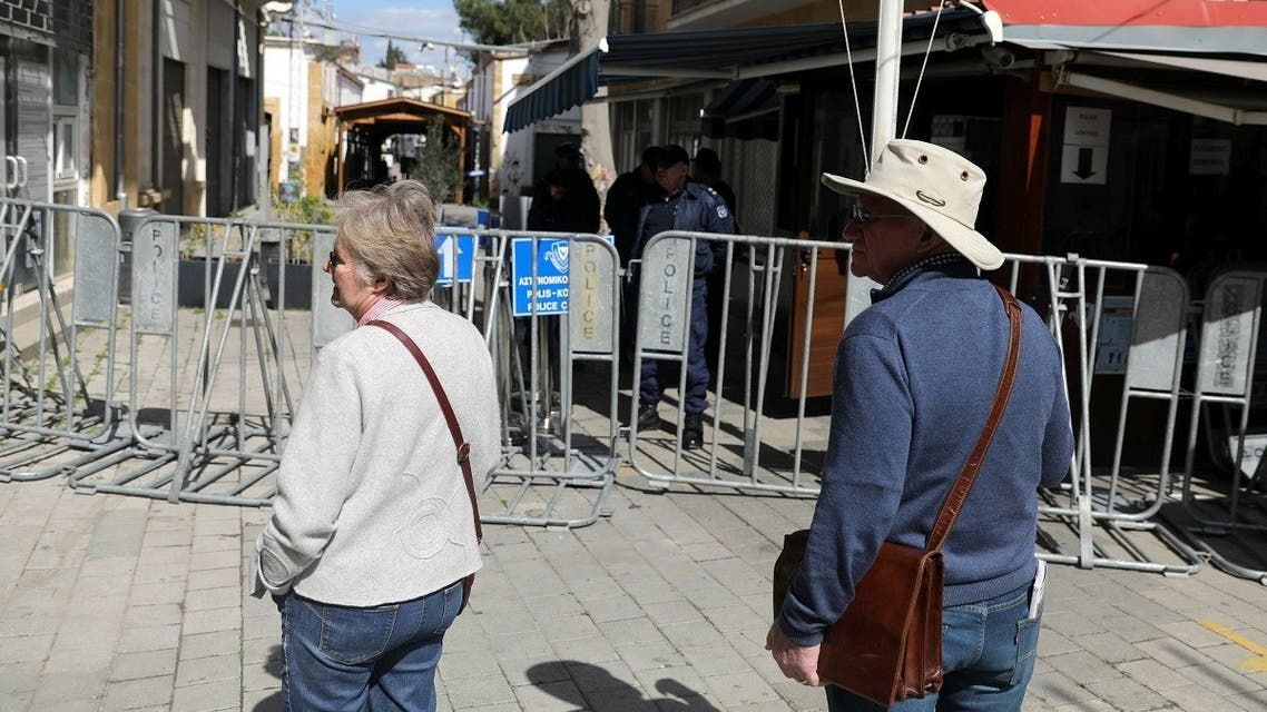 Tourists walks near the closed Ledra checkpoint of the UN-controlled buffer zone, after authorities declared the crossing temporarily shut to curb the spread of the coronavirus in Nicosia, Cyprus February 29, 2020. (Reuters/Yiannis Kourtoglou)