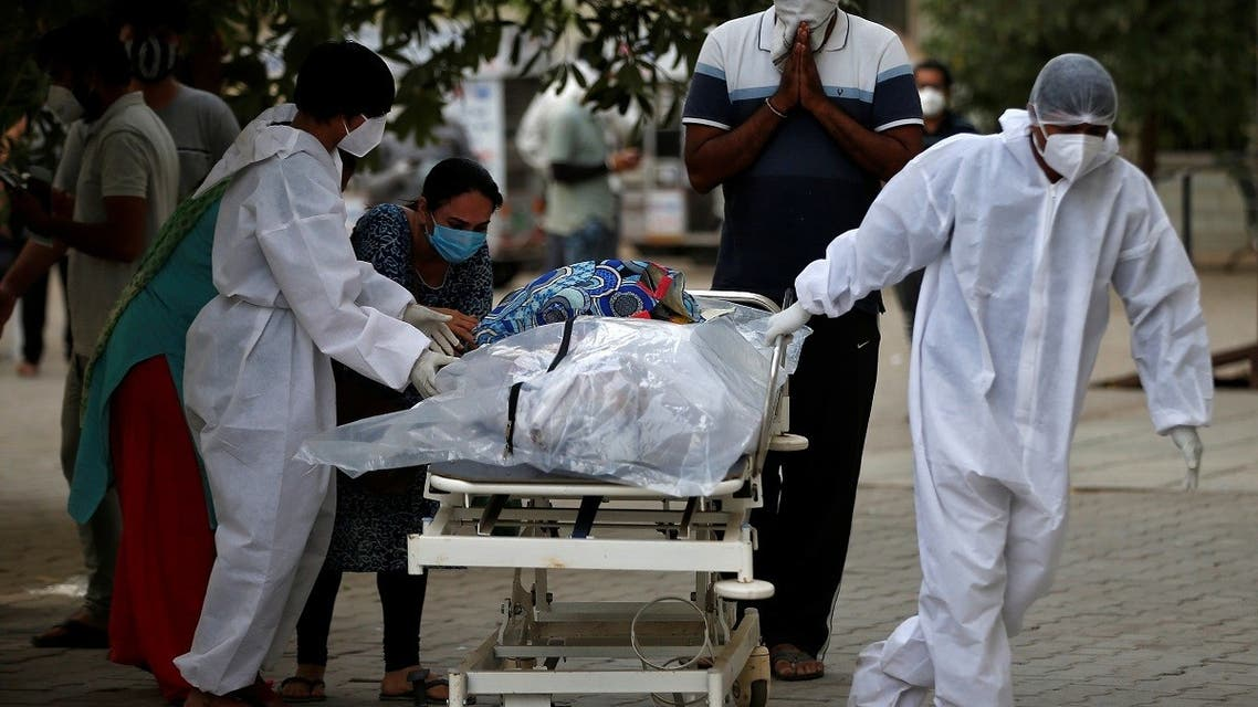 Relatives react as a healthcare worker pulls a stretcher carrying the body of a person, who died from COVID-19, at a mortuary, in Ahmedabad, India, April 26, 2021. (Reuters)