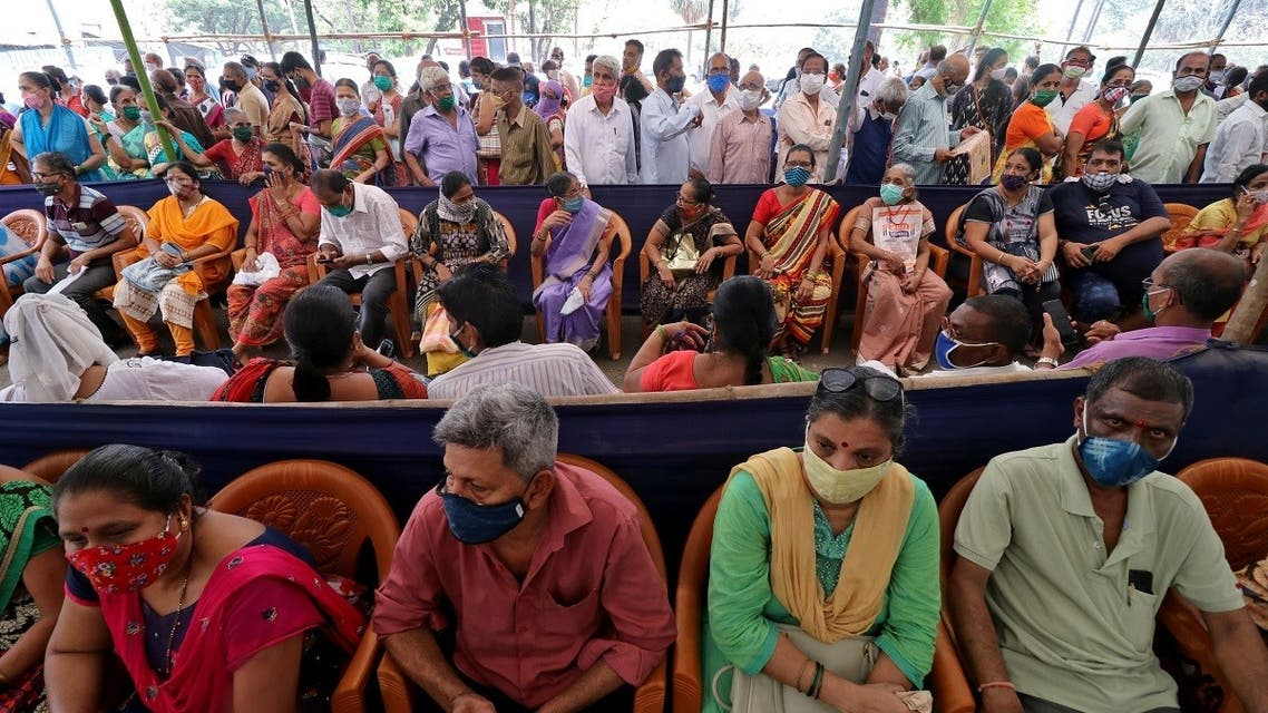 People wearing protective face masks wait to receive a vaccine for the coronavirus at a vaccination centre in Mumbai, India, on April 26, 2021. (Reuters)