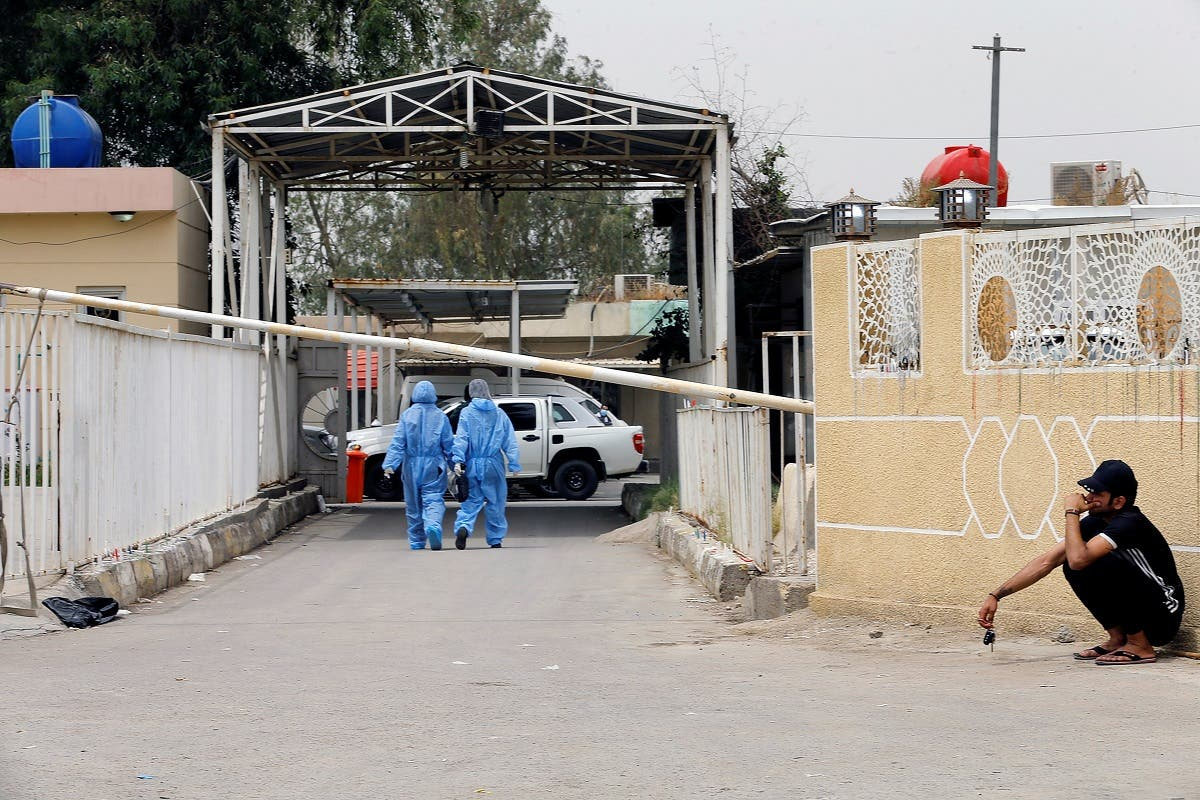 Medical staff members walk near the main entrance of Ibn Khatib hospital where a fire was sparked by an oxygen tank explosion, in Baghdad, Iraq, April 26, 2021. (Reuters/Thaier Al-Sudani)
