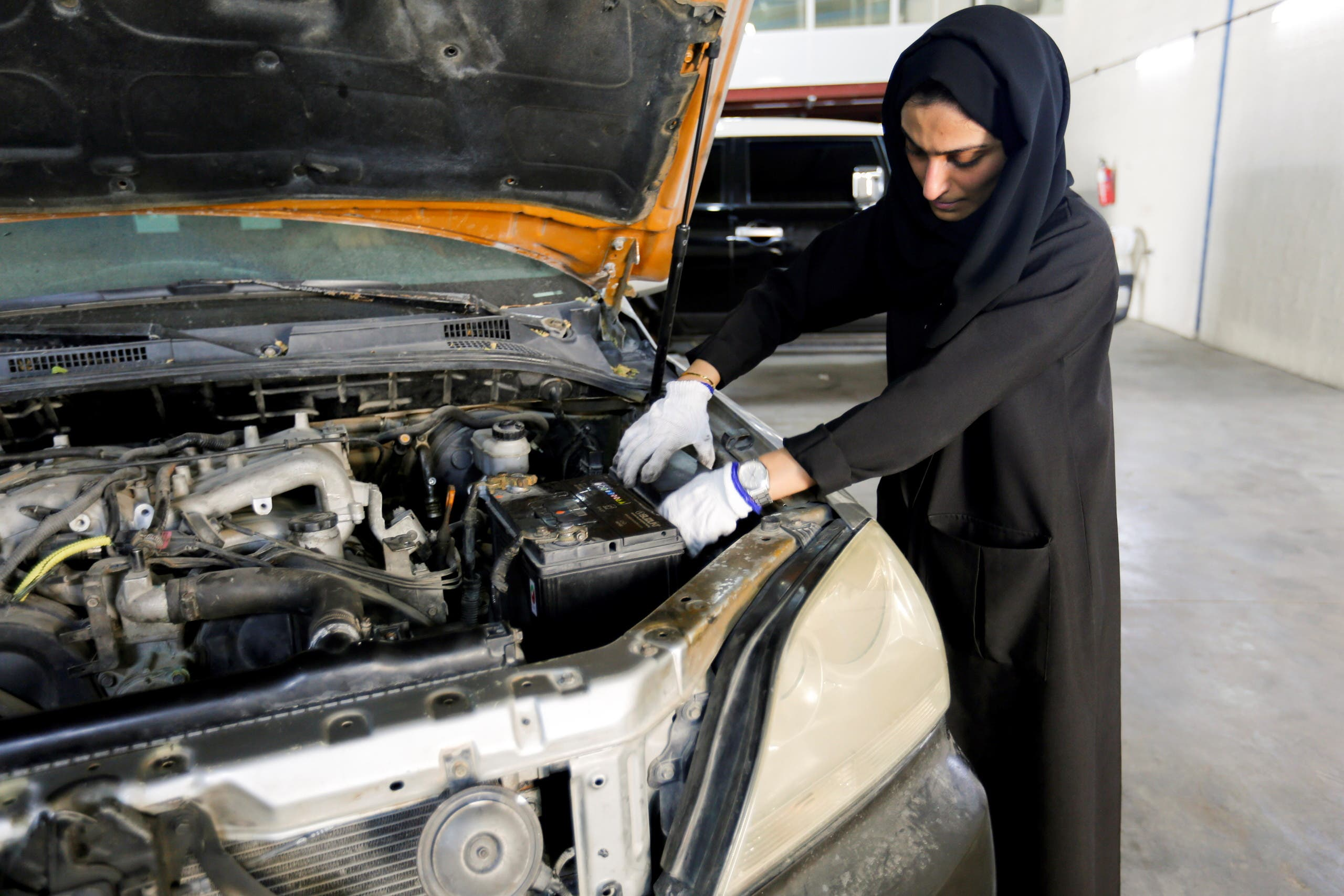 Huda al-Matrooshi, 36, an Emirati woman who owns and runs a car repair garage, checks a car at her garage in Sharjah, United Arab Emirates April 21, 2021. (Reuters)