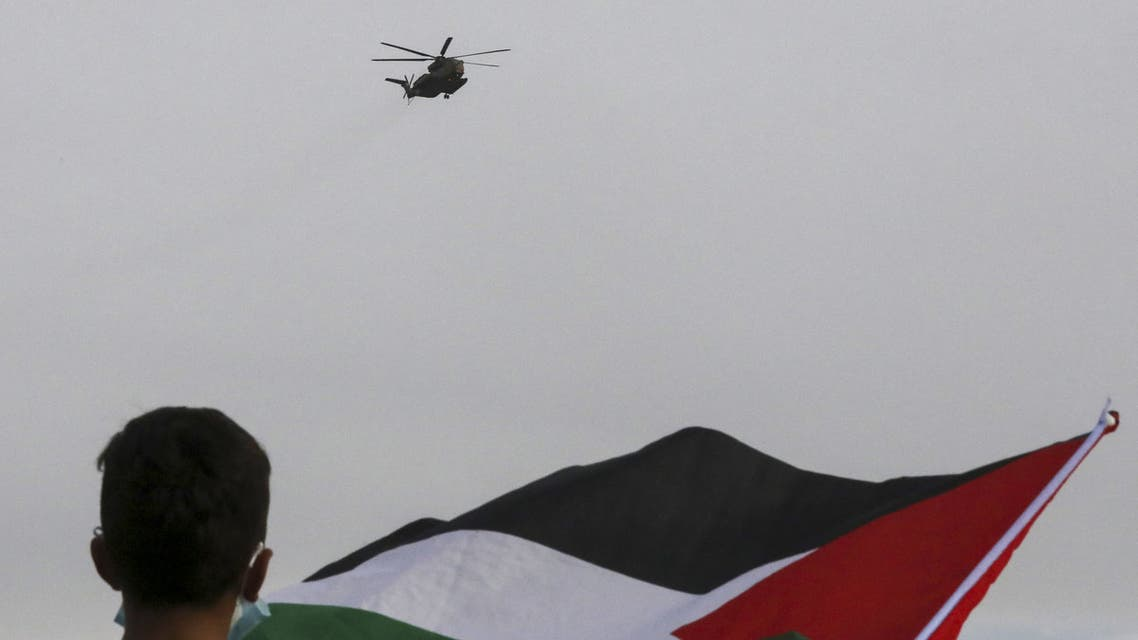 An Israeli army helicopter carrying Israeli Prime Minister Benjamin Netanyahu flies over a demonstrator waving the Palestinian flag during a protest in the Palestinian village of Susya, south of Yatta town, in the occupied West Bank on March 14, 2021. (File photo: AFP)