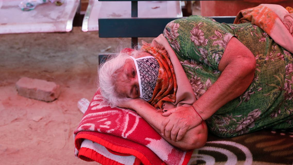A woman suffering from a breathing difficulty due to the coronavirus disease (COVID-19) waits to receive oxygen support for free outside a Gurudwara (Sikh temple) in Ghaziabad, India, April 27, 2021. REUTERS/Adnan Abidi
