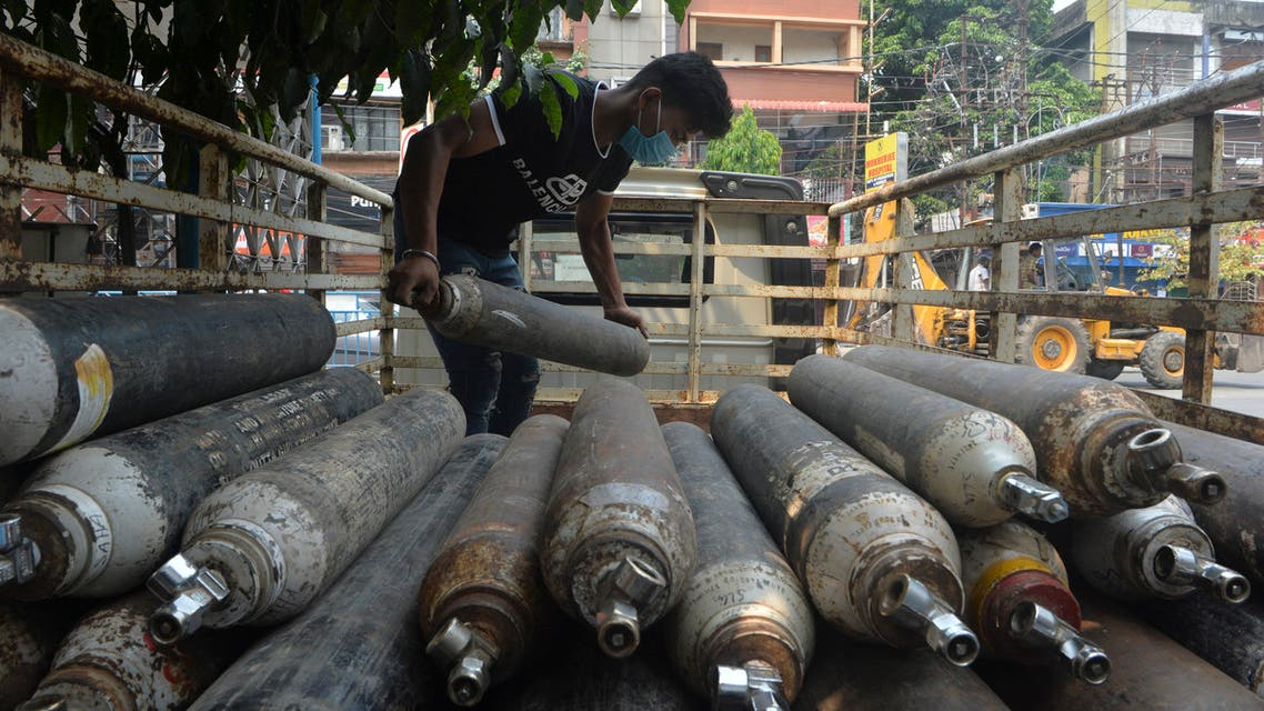A man unloads empty oxygen cylinders for refill at an oxygen supply agency amidst rising Covid-19 coronavirus cases, in Siliguri on April 28, 2021. (File photo: AFP)