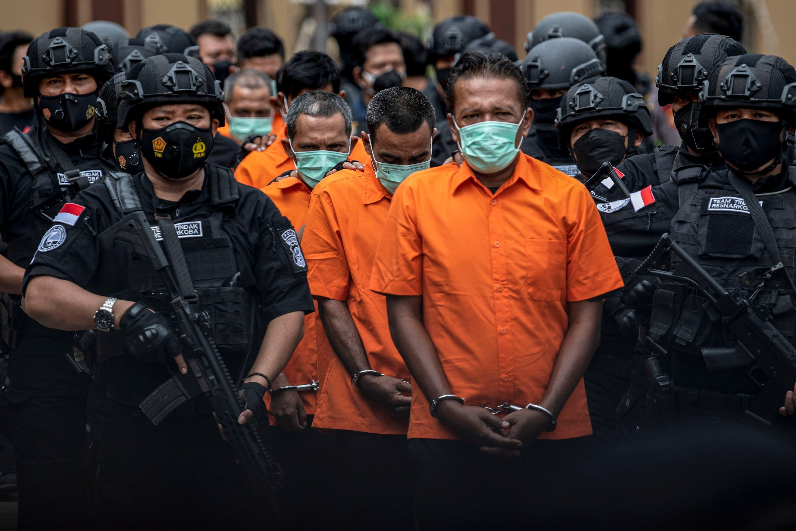 Indonesia Police officers escort suspected drug smugglers during media conference in Jakarta. (Reuters)