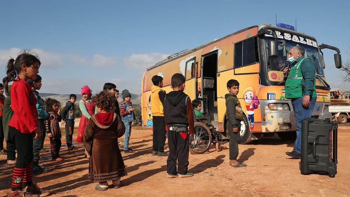 Children take part in an outdoor activity outside a special bus used as a makeshift classroom in the north of Syria's northwestern rebel-held Idlib, Feb. 7, 2021. (AFP)