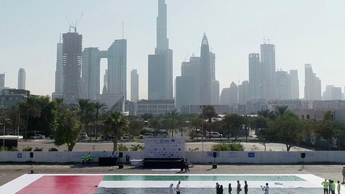 A UAE mosaic flag measuring 498.33 m² breaking a Guiness World Record with Dubai's skyline in the background. (WAM)