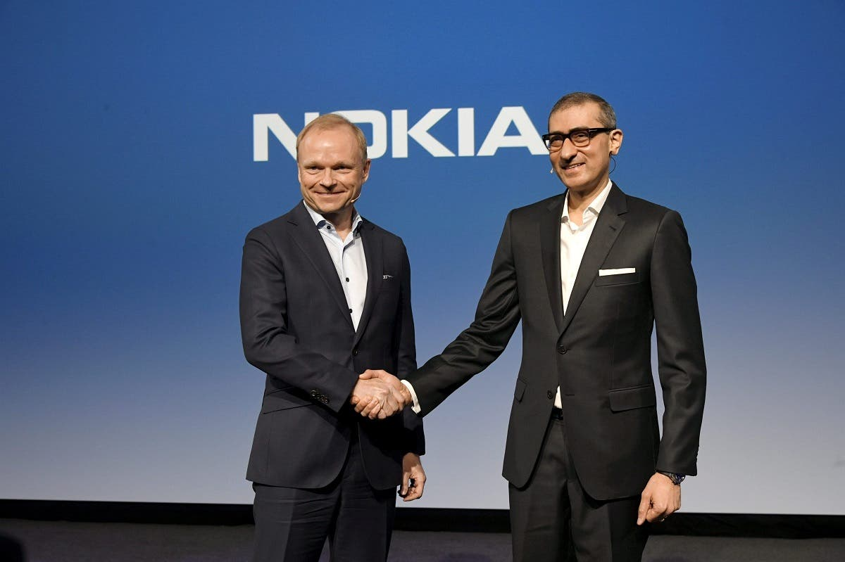 Nokia's new President and CEO Pekka Lundmark shakes hands with resigning President and CEO Rajeev Suri (R) after a news conference at the Nokia headquarters in Espoo, Finland, on March 2, 2020. (Reuters)