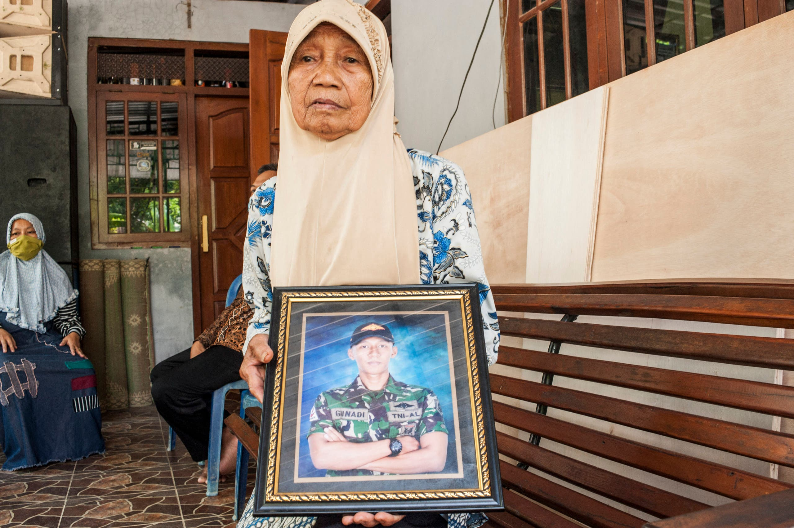 Sarikem holds a photo of her grandson Gunadi Fajar Rahmanto at their home in Yogyakarta on April 26, 2021, a crew member of the submarine that disappeared off the coast of Bali and has been found cracked into pieces on the seafloor with all 53 crew killed in the disaster. (File photo: AFP)