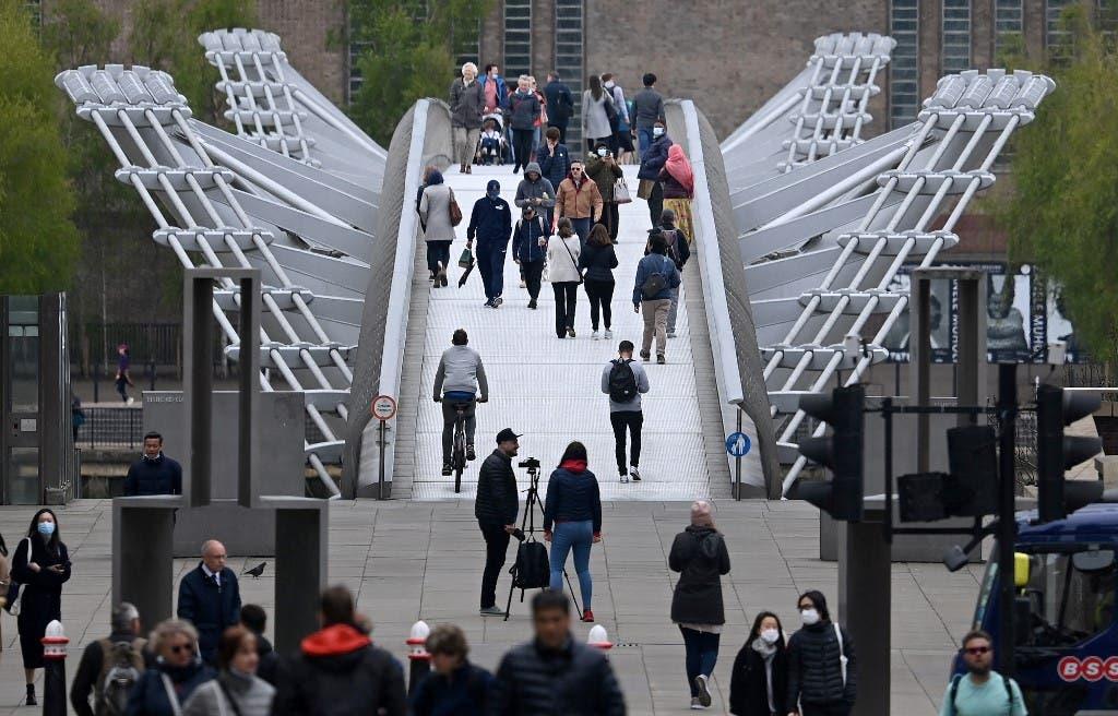 Pedestrians walk over the Millennium Bridge in the City of London on April 29, 2021. (AFP)