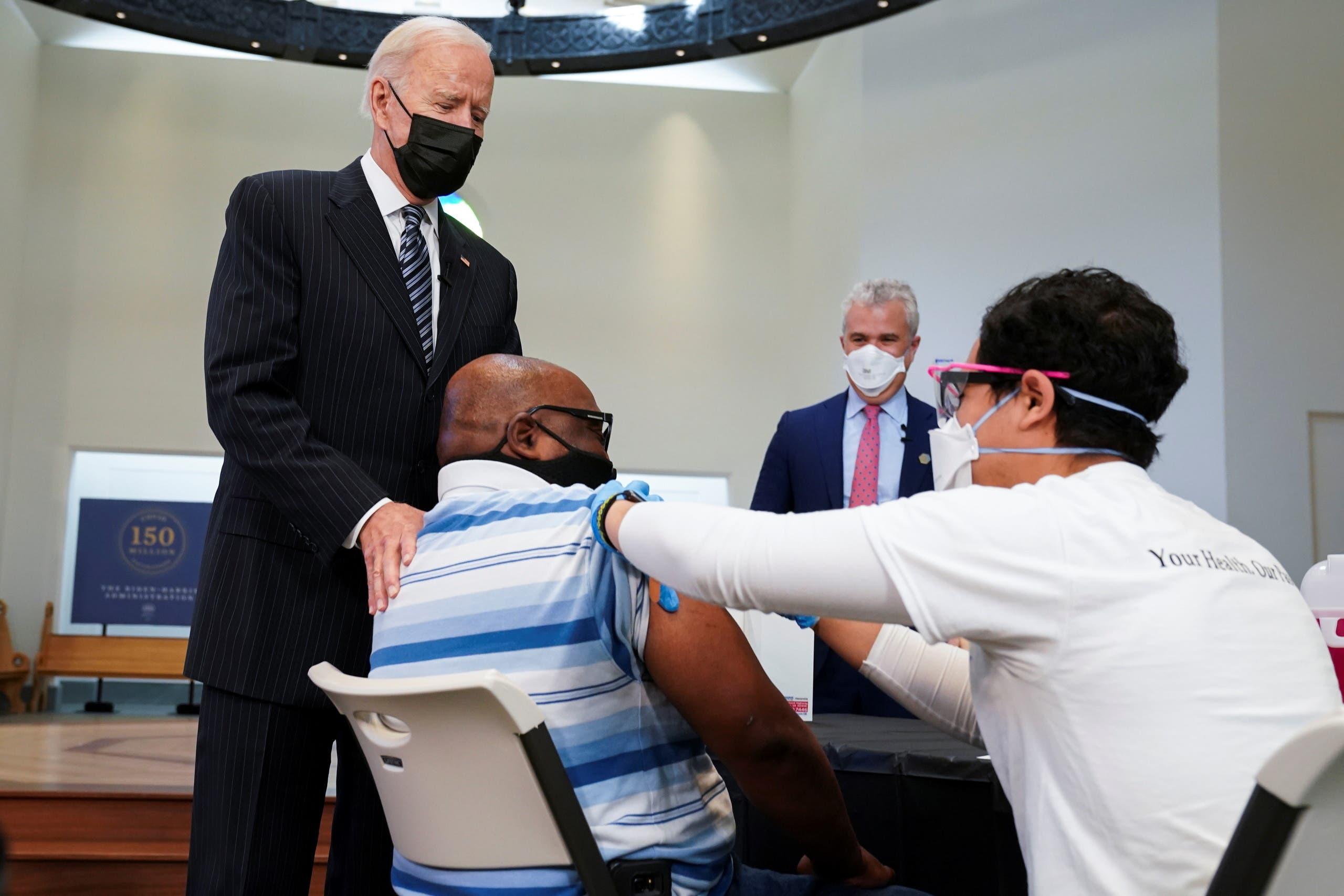 الرئيس الأميركي في زيارة لأحد مراكز التطعيم (رويترز)