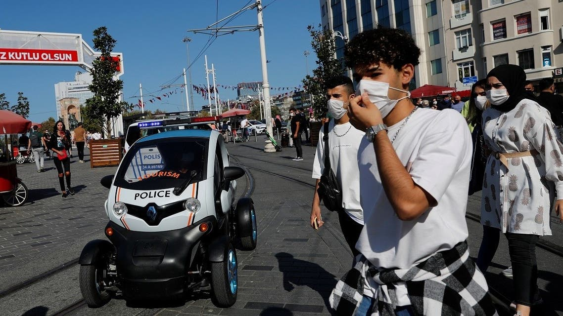 A member of Tourism Police sitting in a car patrols against people not wearing protective face masks at the main shopping and pedestrian street of Istiklal as the spread of the coronavirus continues, in Istanbul, Turkey, on September 27, 2020. (Reuters)