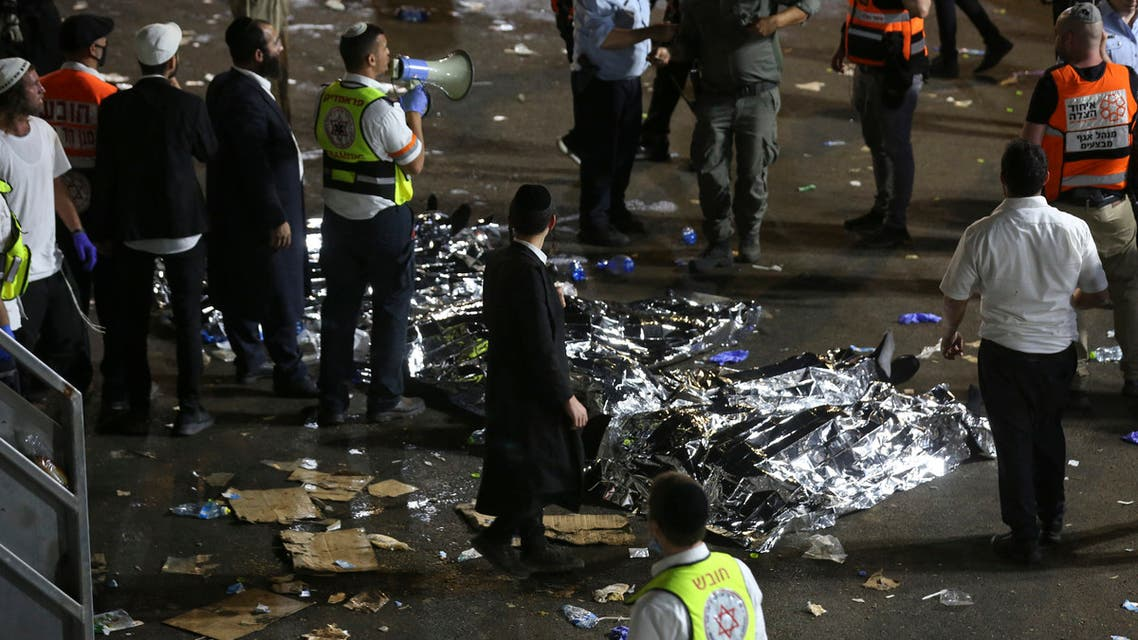 ltra-Orthodox Jewish men stand next to covered bodies after dozens of people were killed and others injured after a grandstand collapsed in Meron, Israel, where tens of thousands of people were gathered to celebrate the festival of Lag Ba'omer at the site in northern Israel early on April 30, 2021. (File photo: AFP)
