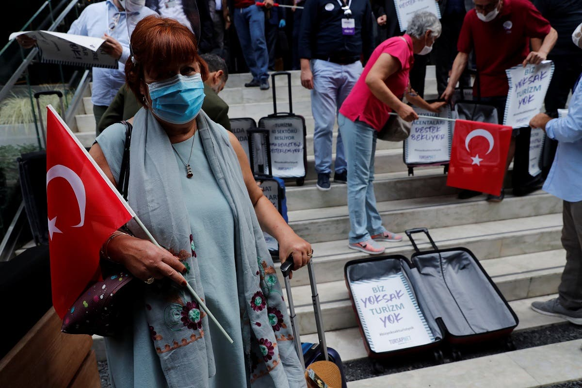 Travel agency owners display empty suitcases following a press statement demanding government's financial support for the tourism business as the spread of the coronavirus continues, in Istanbul, Turkey, on October 6, 2020. (Reuters)