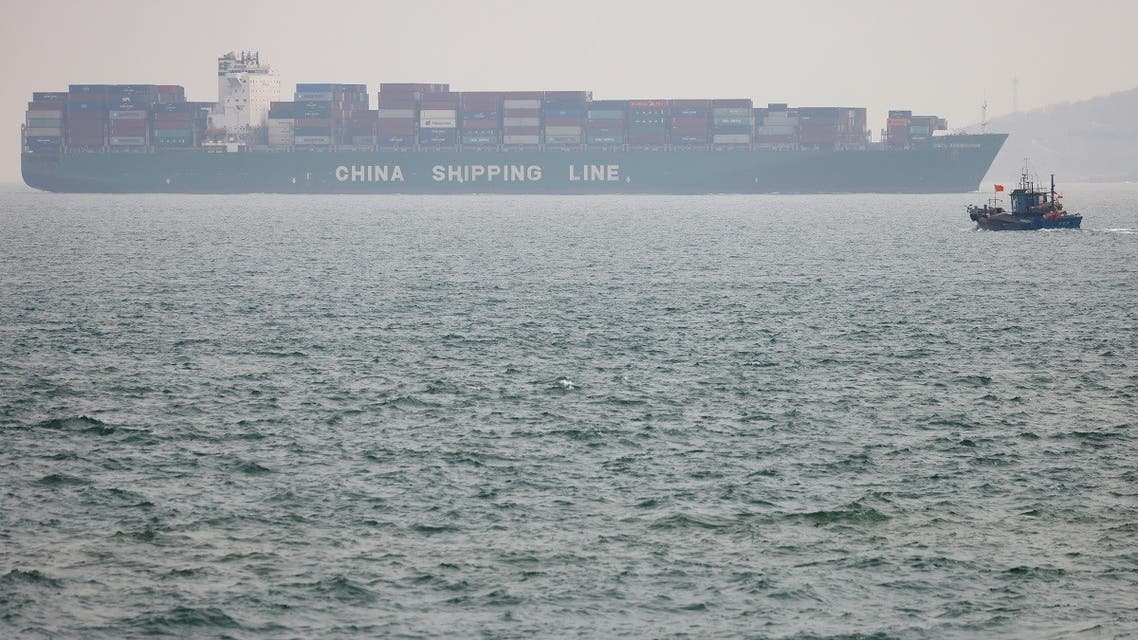 A fishing boat is seen near a China Shipping Container Lines (CSCL) vessel off the coast of Qingdao, Shandong province, China, following an oil spill in the Yellow Sea caused by a collision between tanker A Symphony and bulk vessel Sea Justice off Qingdao port, April 29, 2021. (Reuters)