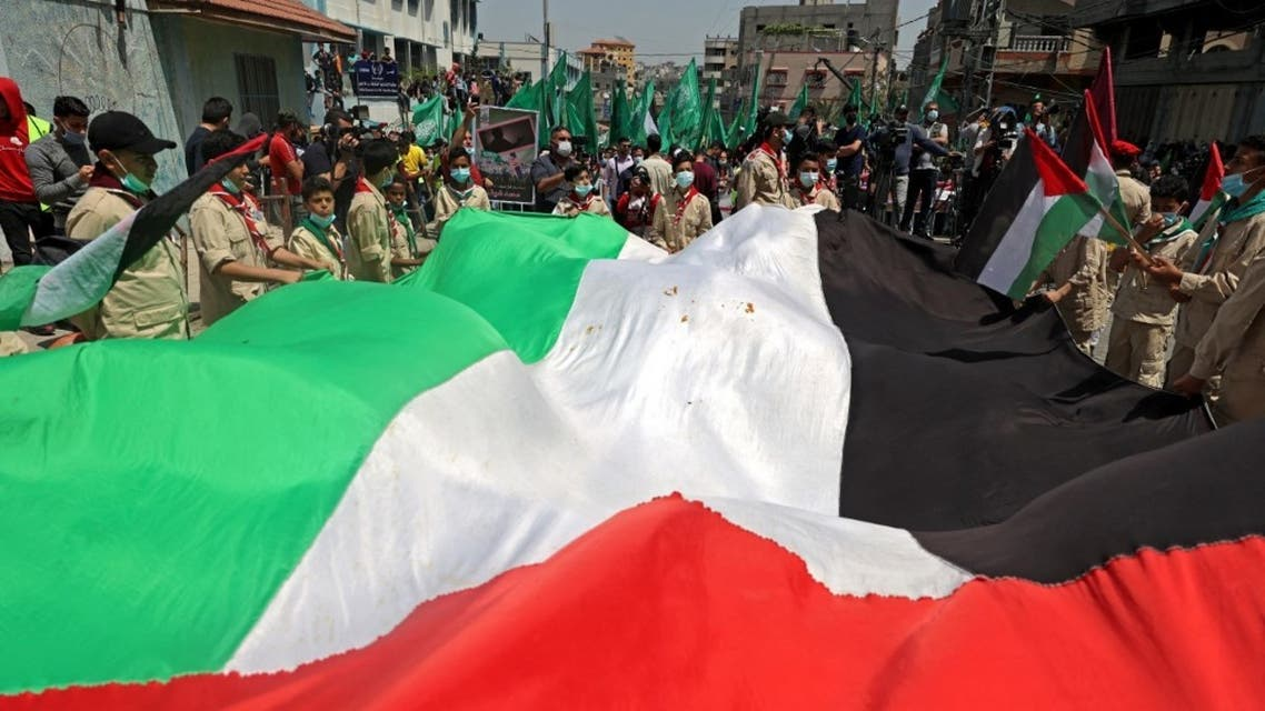 Palestinian protesters wave national (foreground) and Hamas movement flags during a demonstration in the Jabalia refugee camp in the Gaza Strip on April 30, 2021, following the postponement of the upcoming Palestinian elections which were supposed to take place next month. (AFP)