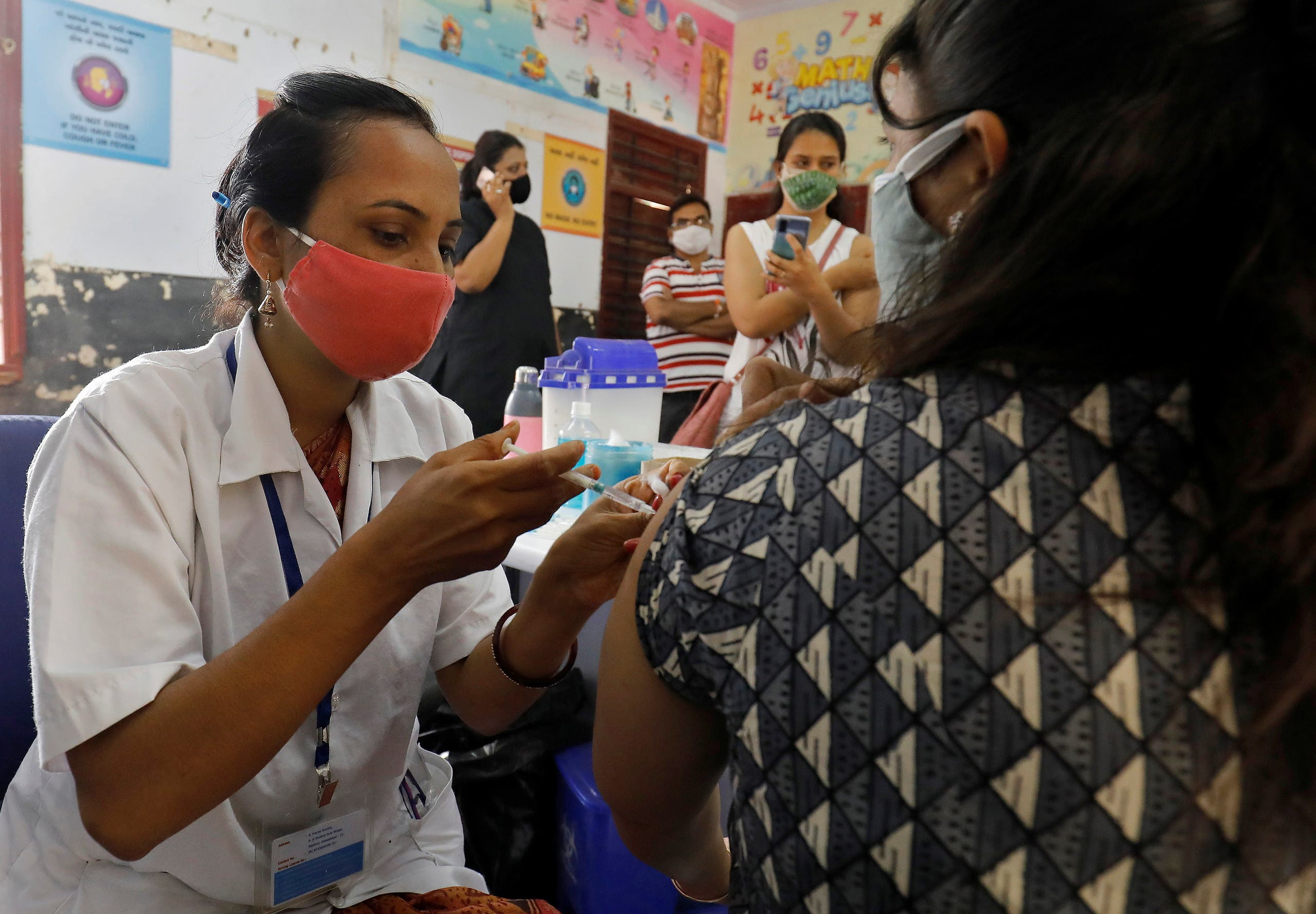 A healthcare worker gives a dose of COVISHIELD, a coronavirus disease (COVID-19) vaccine manufactured by Serum Institute of India, to a woman inside a classroom of a school, which has been converted into a temporary vaccination centre, in Ahmedabad, India, May 1, 2021. (Reuters)