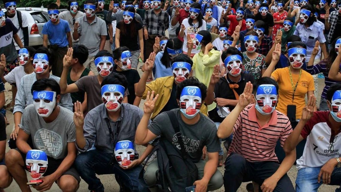 This handout from the Burma Associated Press (BAP) taken and received on April 4, 2021 shows protesters making the three-finger salute while wearing masks that express what they say is Chinese interference in the UN's handling of Myanmar affairs after the military coup in Yangon's Kamayut township. (AFP)