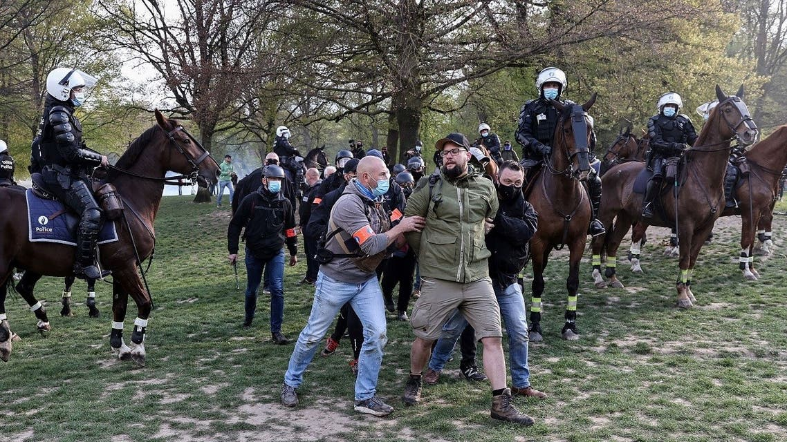 Belgian police officers arrest a protester during the second edition of the unauthorized 'La Boum - L'Abime' festival, a protest against the COVID-19 health restrictions, at the Bois de La Cambre park in Brussels on may 1, 2021. (Kenzo Tribouillard/AFP)