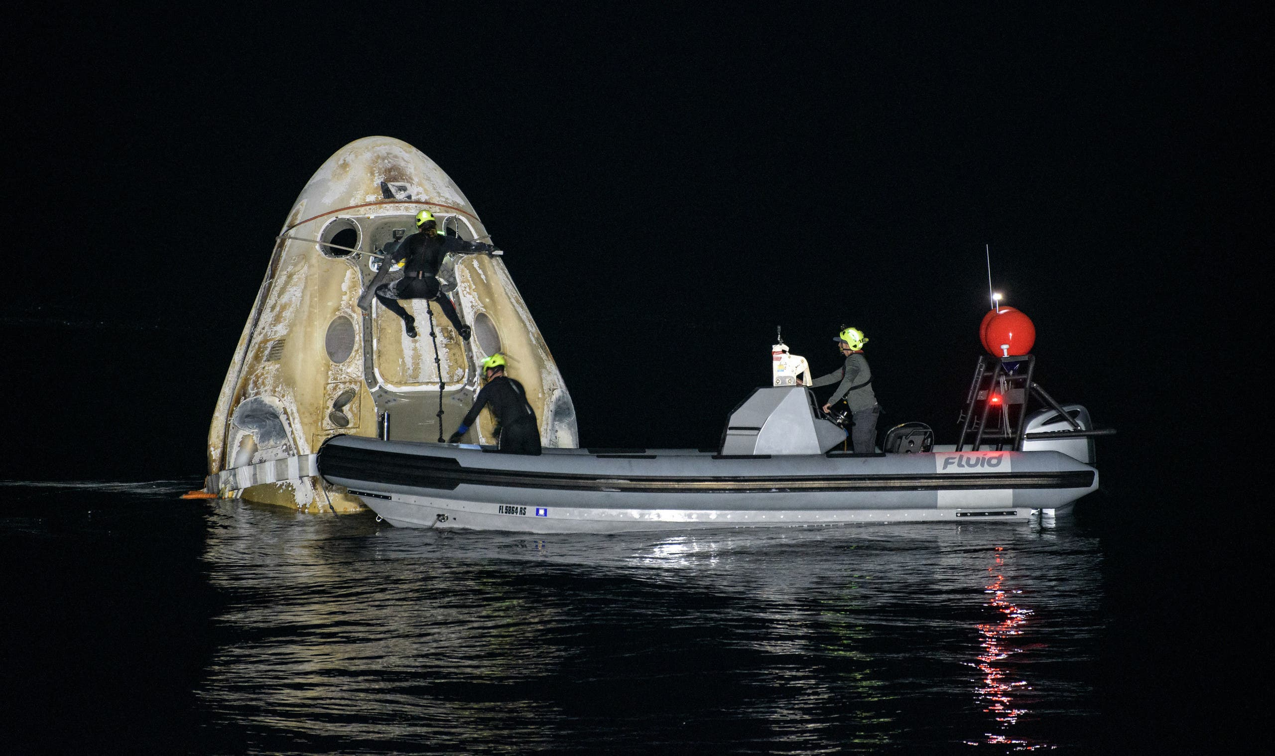 This handout image courtesy of NASA and made available on May 2, 2021, shows the support teams working around the SpaceX Crew Dragon Resilience spacecraft shortly after it landed with NASA astronauts Mike Hopkins, Shannon Walker, and Victor Glover, and Japan Aerospace Exploration Agency (JAXA) astronaut Soichi Noguchi aboard in the Gulf of Mexico off the coast of Panama City, Florida on May 2, 2021. (AFP)