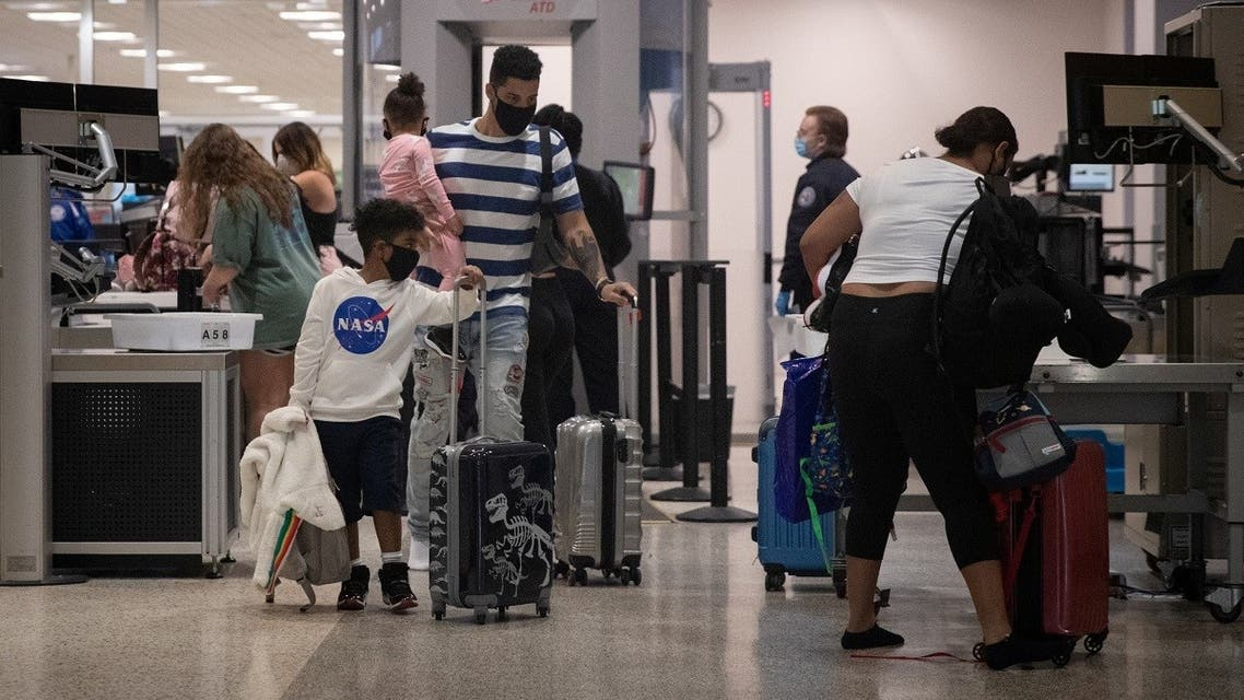 A family wears face masks as they pass security at Terminal A of IAH George Bush Intercontinental Airport amid the coronavirus outbreak in Houston, Texas, US, July 21, 2020. (Reuters/Adrees Latif)