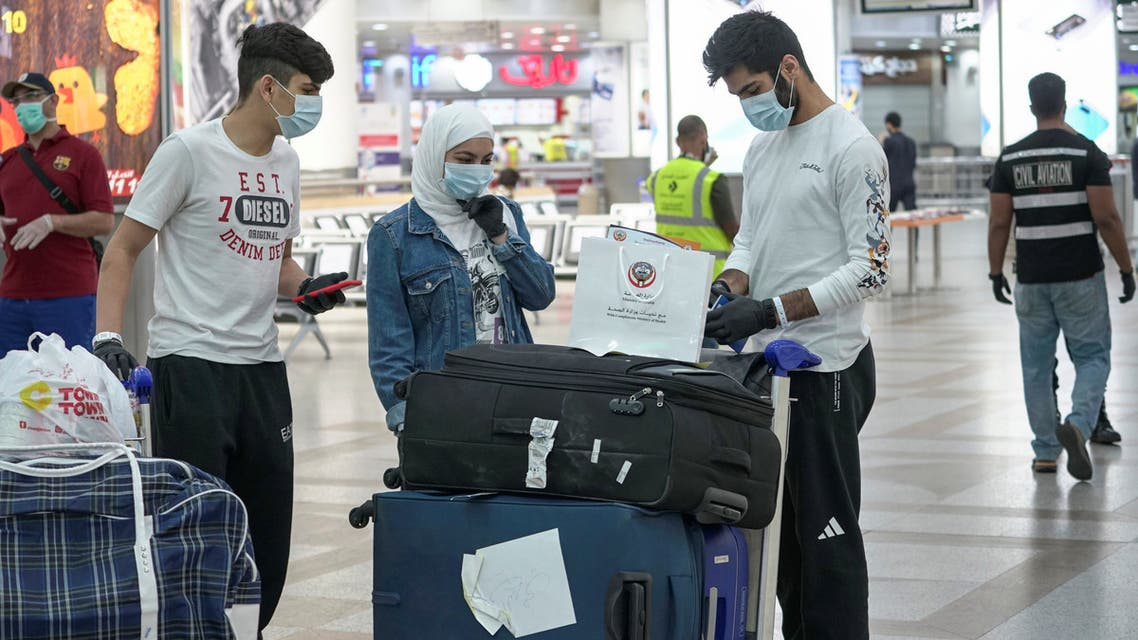 Repatriated Kuwaitis from Amman, wearing protective face masks, following the outbreak of the coronavirus disease (COVID-19), prepare their luggage while arriving at Kuwait Airport, Kuwait April 21, 2020. (Reuters)