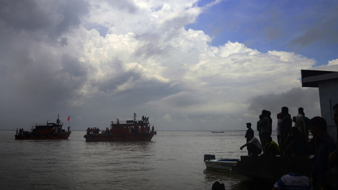 Bangladeshi rescue teams search the water as onlookers gather where an overloaded ferry capsized in the Padma river in Munshiganj, some 30 kilometres south of the capital Dhaka, on August 6, 2014. The owner and captain of a heavily overloaded river boat that sank in Bangladesh are facing criminal charges over the disaster, in which more than 130 people are feared drowned. The ferry was only licensed to carry 85 passengers, but had more than 200 on board when it went down in rough conditions in Munshiganj, around 30 kilometres (20 miles) south of Dhaka, on August 4, 2014. Police said they had launched a manhunt for the owner of the vessel, which rescue workers have still not been able to locate, more than 48 hours after the disaster. AFP PHOTO/Munir uz ZAMAN