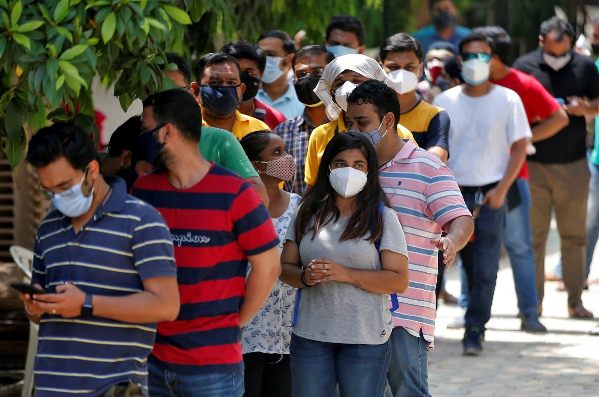 People wearing protective face masks wait to receive a dose of COVISHIELD, a coronavirus  vaccine manufactured by Serum Institute of India, outside a vaccination centre in Ahmedabad, India, on May 1, 2021. (Reuters)