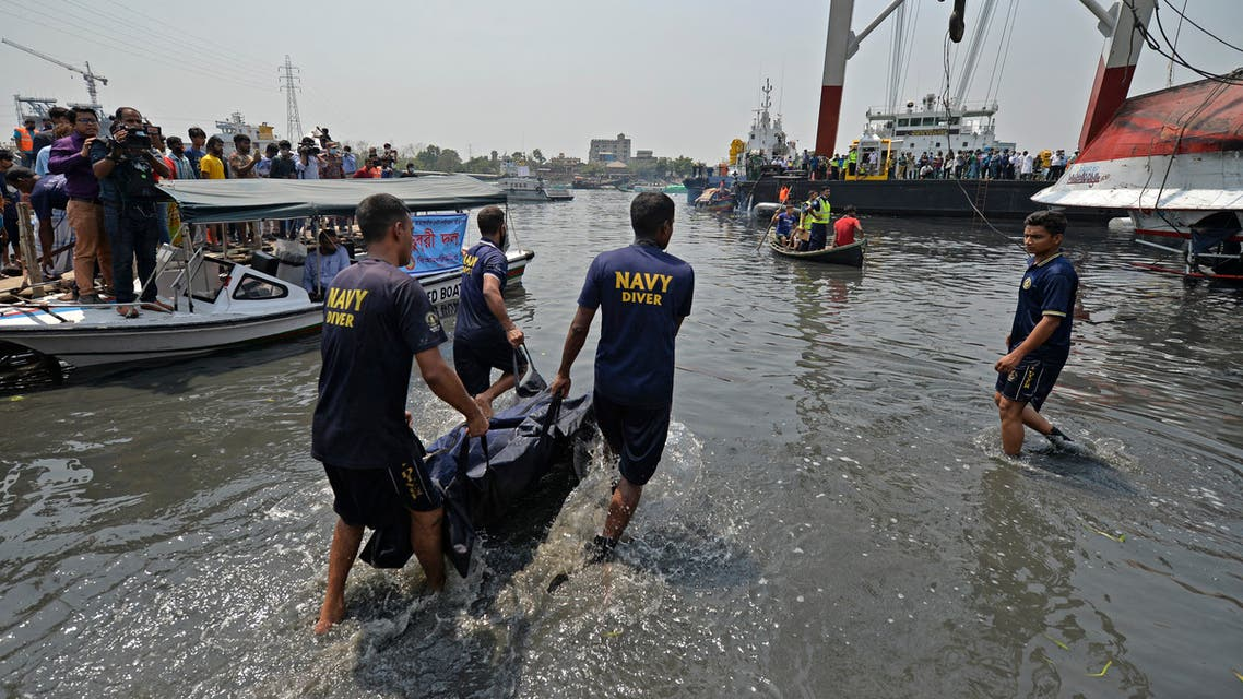 Divers carry a dead body after recovering from the capsized boat in Shitalakshya River, in Narayanganj on April 5, 2021.