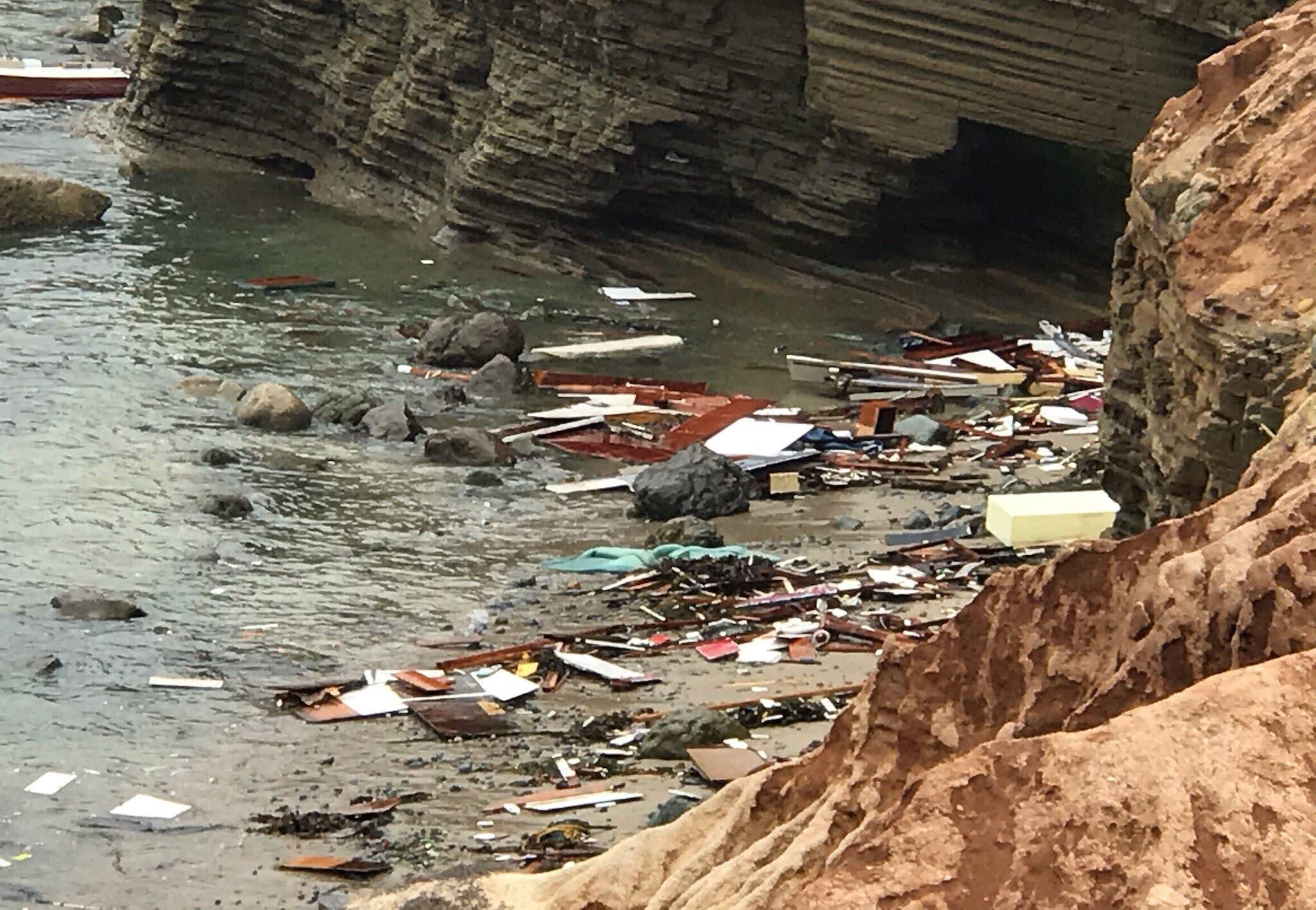 حطام القارب يطفو على المياه قبالة الشاطئ الذي تحطم عليه