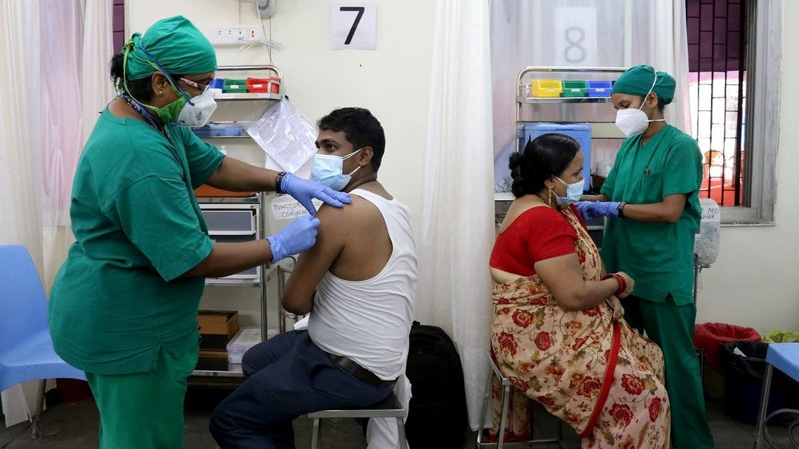 Rohit Gupta, 27 and Nandani Gupta, 42, receive their first dose of COVISHIELD, a coronavirus disease (COVID-19) vaccine manufactured by Serum Institute of India, at a vaccination center in Mumbai, India, on May 3, 2021. (Reuters)