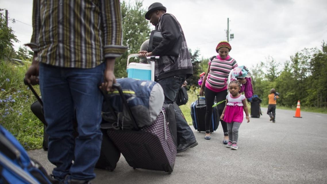 A long line of asylum seekers wait to illegally cross the Canada/US border near Champlain, New York on August 6, 2017. (File photo: AFP)