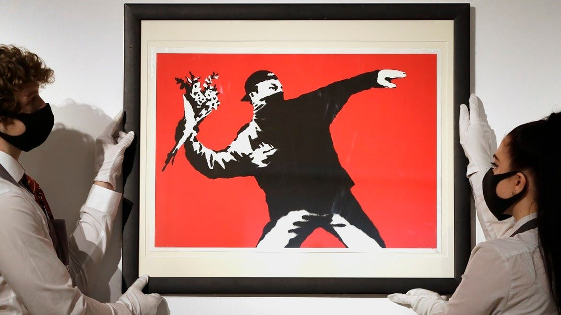 Gallery technicians display a Banksy called Love is in the Air screenprint in colours, 2003, on wove paper, numbered 412/500 in pencil at Christie's auction rooms in London, on March 26, 2021.  (AP)