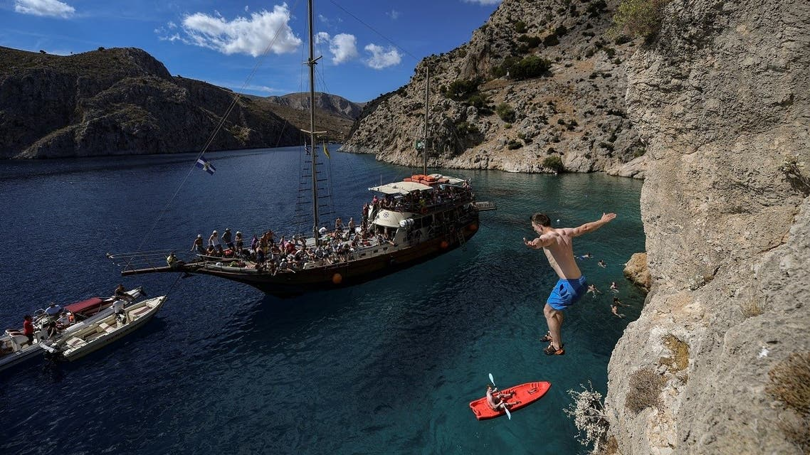 A climber jumps into the sea as he participates in the 2019 annual Climbing Festival in the island of Kalymnos on October 4, 2019. (Aris Messinis/AFP)