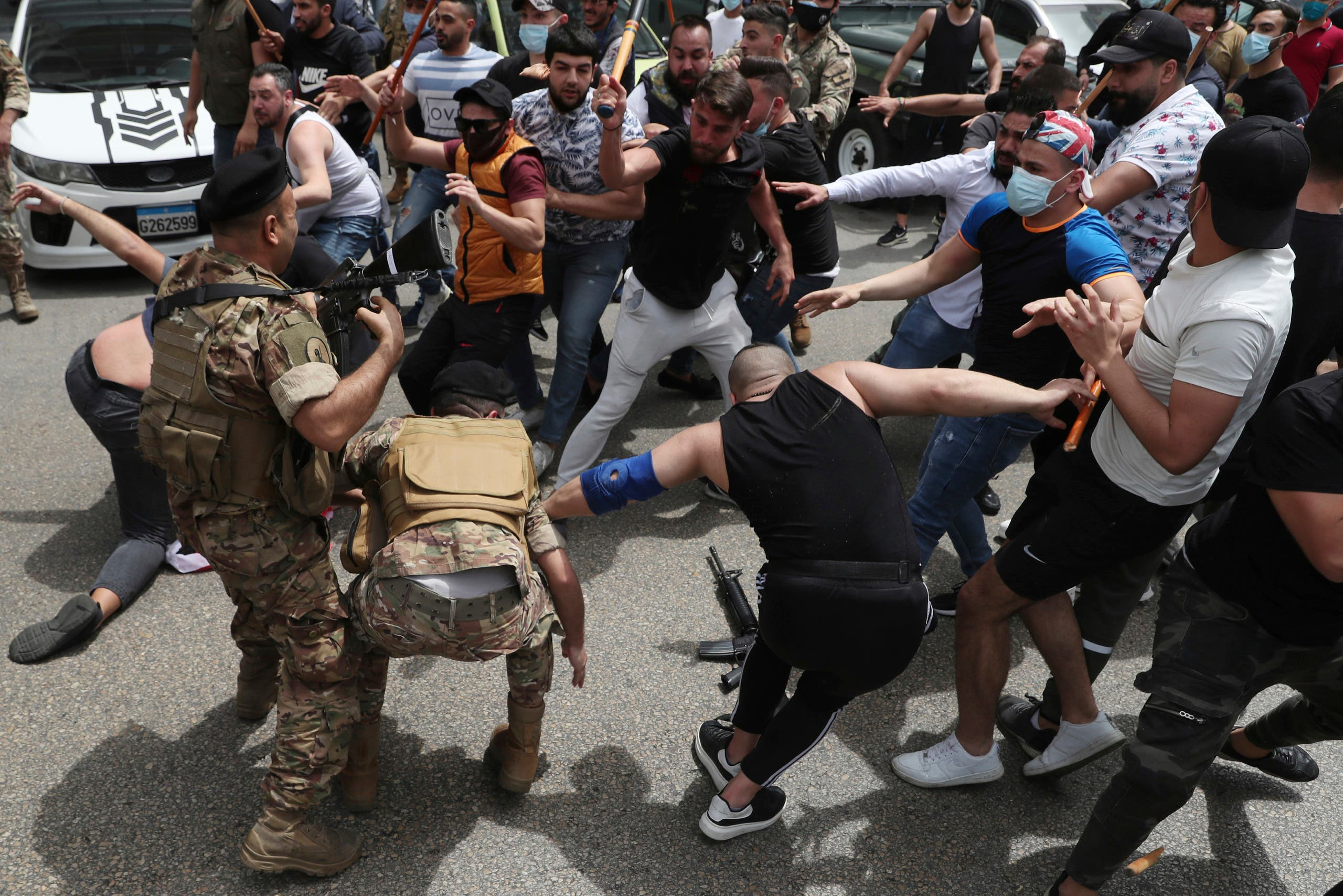 In this April 19, 2021 file photo, opponents of Judge Ghada Aoun try to strip an army soldier of his rifle as scuffles break out during a sit-in outside the Justice Palace, in Beirut, Lebanon. (AP)