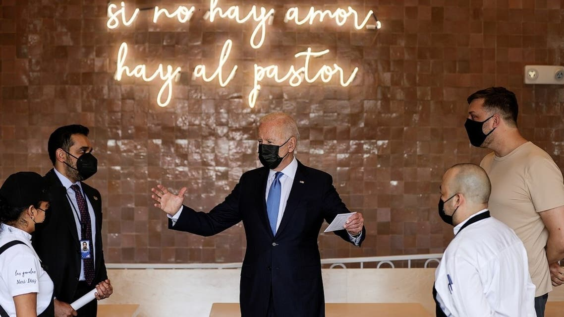 """US President Joe Biden stands under a sign reading """"if there is no love, there is still al pastor (tacos)"""" while being greeted as he visits Las Gemelas Taqueria in the Union Market neighborhood in Washington, US, on May 5, 2021. (Reuters)"""