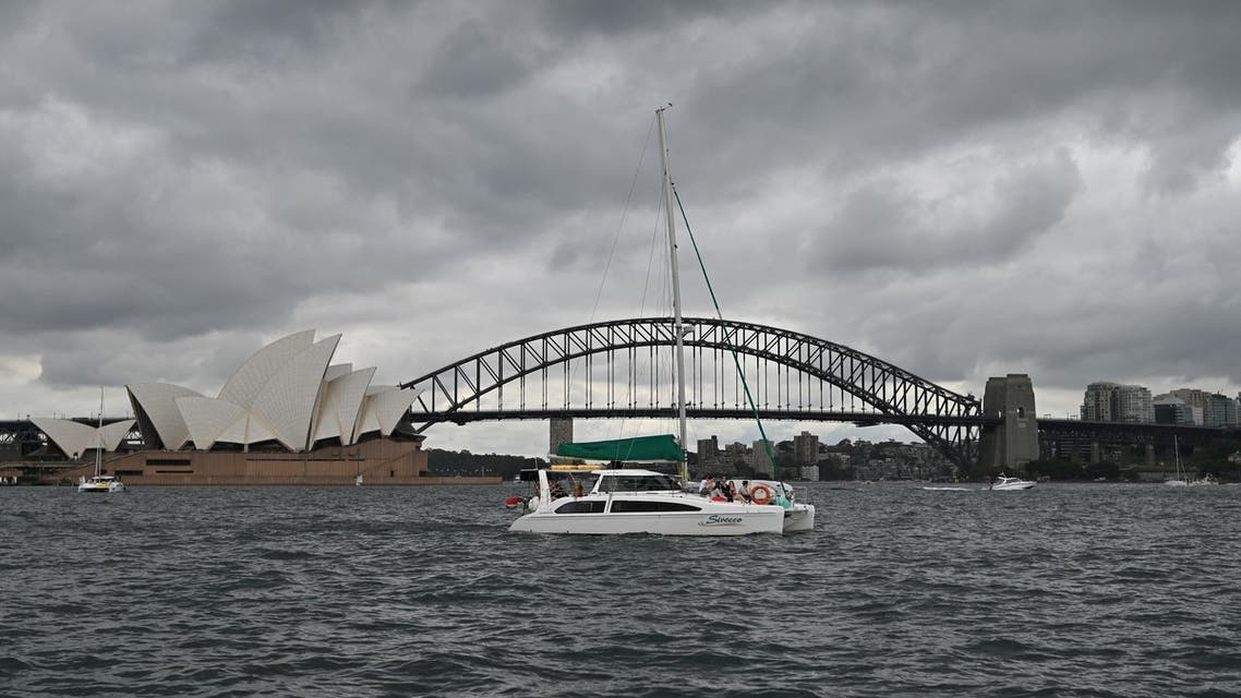 People sail past the Opera House and Harbour Bridge in Sydney on December 20, 2020, after authorities introduced a fresh round of restrictions to control a growing coronavirus outbreak in the city.