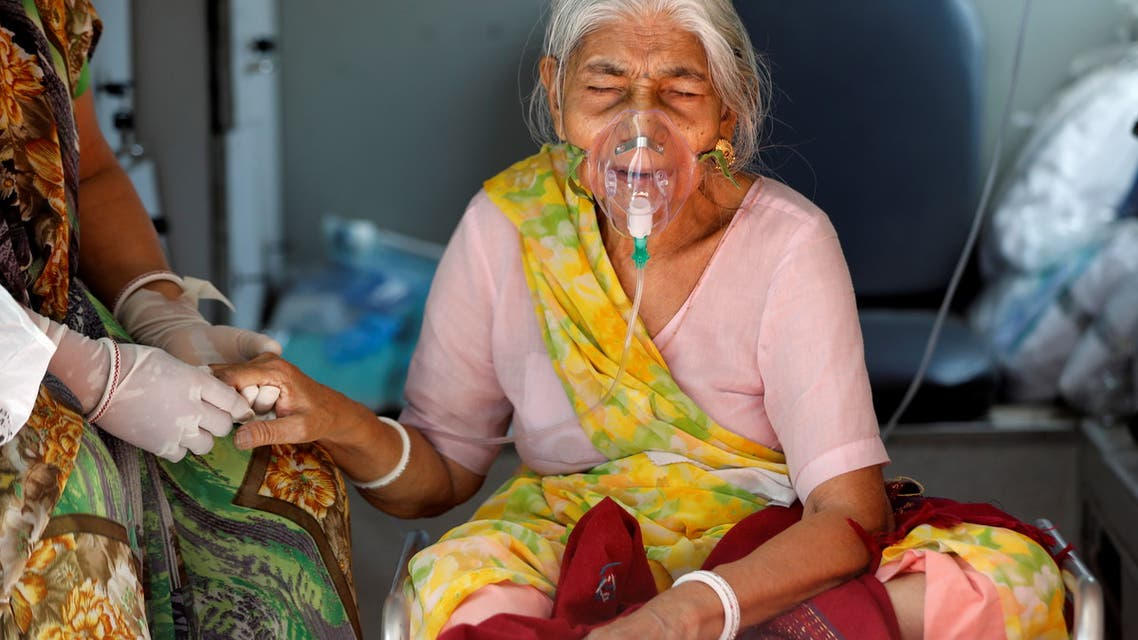 Lilaben Gautambhai Modi, 80, wearing an oxygen mask, sits inside an ambulance as she waits to enter a COVID-19 hospital for treatment, amidst the spread of the coronavirus disease (COVID-19), in Ahmedabad, India, May 5, 2021. REUTERS/Amit Dave