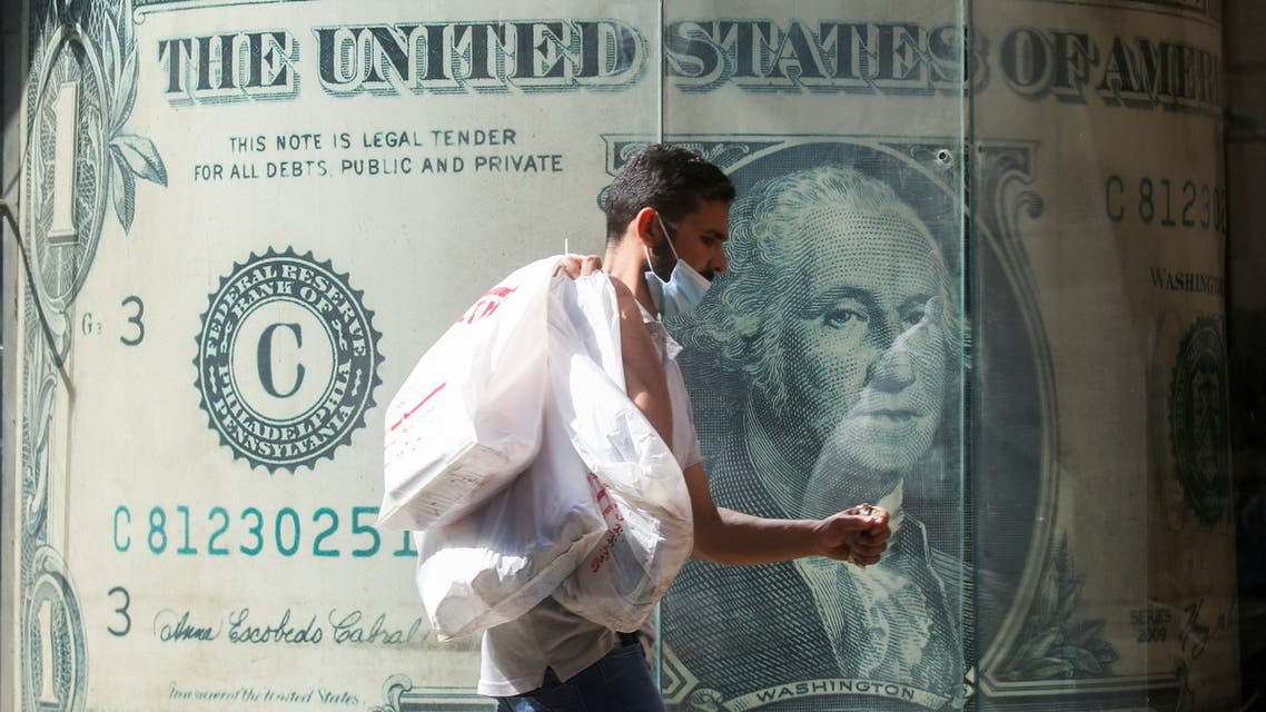 A man wearing a protective face mask walks in front of a currency exchange bureau advertisement showing an image of the U.S. dollar amid the coronavirus disease (COVID-19) pandemic in Cairo, Egypt May 5, 2021. (File photo: Reuters)