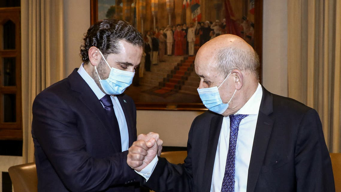 A handout picture provided by the Lebanese photo agency Dalati and Nohra on May 6, 2021 shows Lebanon's prime minister-designate Saad Hariri (L) fist-bumping French Minister for Foreign and European Affairs Jean-Yves Le Drian (R) during their meeting in the capital Beirut. (File photo: AFP)