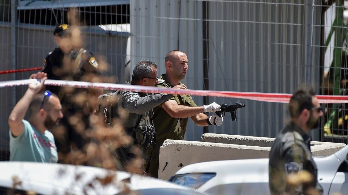 An IDF officer inspects the weapon used by a Palestinian gunmen at the scene of shooting attack in front of the military base of Salem near the West Bank town of Jenin, on May. 7, 2021. (Reuters)