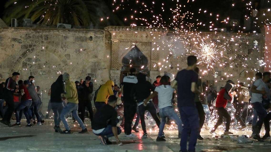 Palestinians react as Israeli police fire stun grenades during clashes at the compound that houses Al-Aqsa Mosque, May 7, 2021. (Reuters)