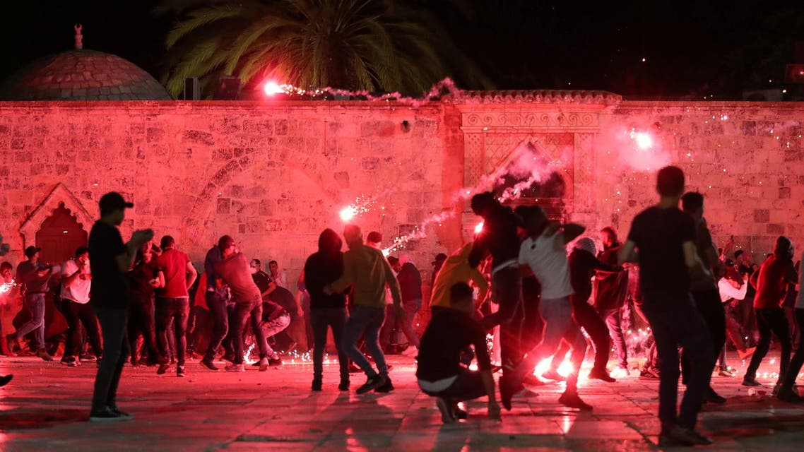 Palestinians react as Israeli police fire stun grenades during clashes at the compound that houses Al-Aqsa Mosque. (Reuters)
