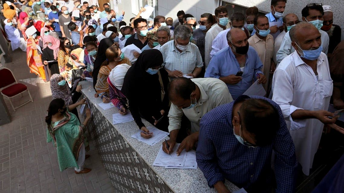 People stand in queues while they wait their turn to receive the first shot of the Sinopharm COVID-19 vaccine at a vaccination center in Karachi, Pakistan, Saturday, May 8, 2021. (AP/Fareed Khan)